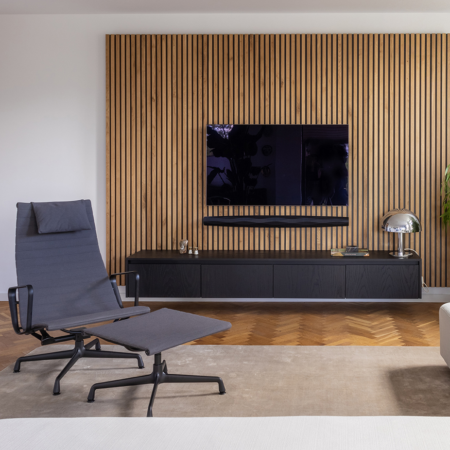 De wand achter de televisie is van massief eiken regelwerk en steekt mooi af tegen het zwevend meubel van eiken zwart gebeitst.
