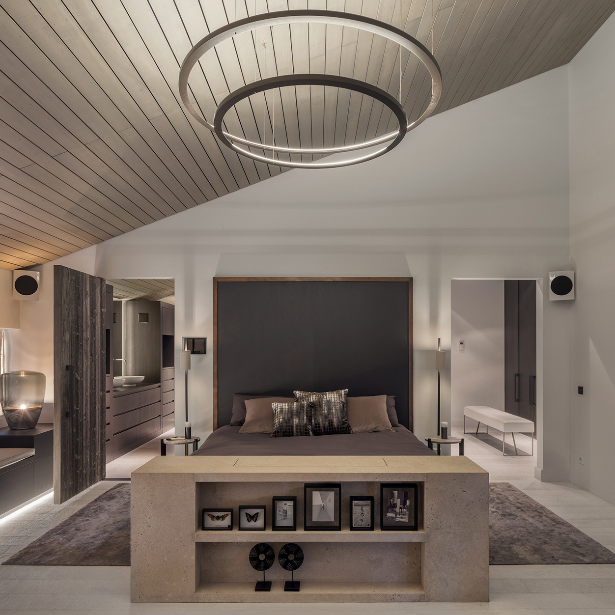 Het tv-meubel aan het voeteneinde van het tweepersoonsbed is voorzien van een praktisch liftsysteem, waardoor de televisie uit het zicht verdwijnt. Ook dit meubel is in zijn geheel vervaardigd uit Travertin natuursteen.